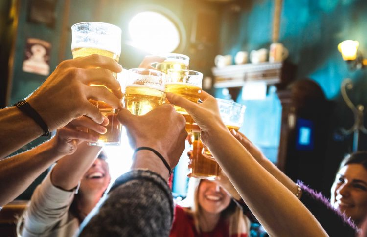 Stock image of a group of people toasting drinks in a bar