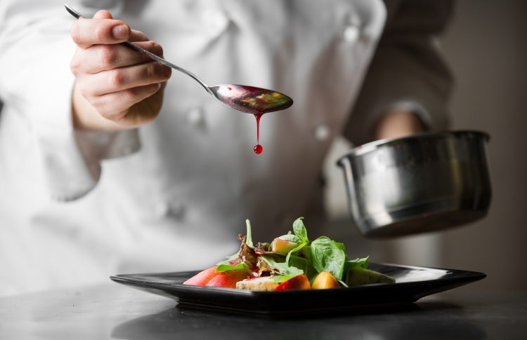 chef pouring sauce on gourmet meal