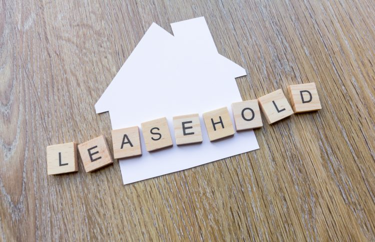 Leasehold spelt in letters over a paper house