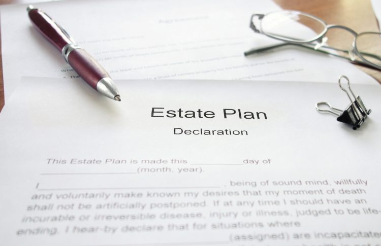 Estate plan declaration document on a table with a pen and glasses