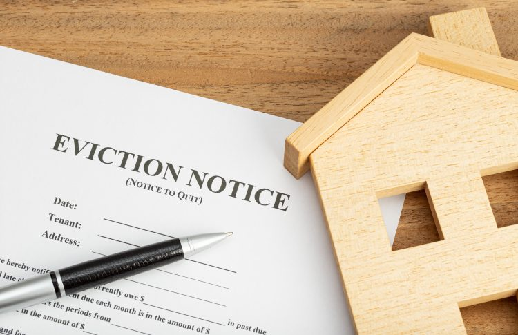 Eviction notice document and toy house on a table