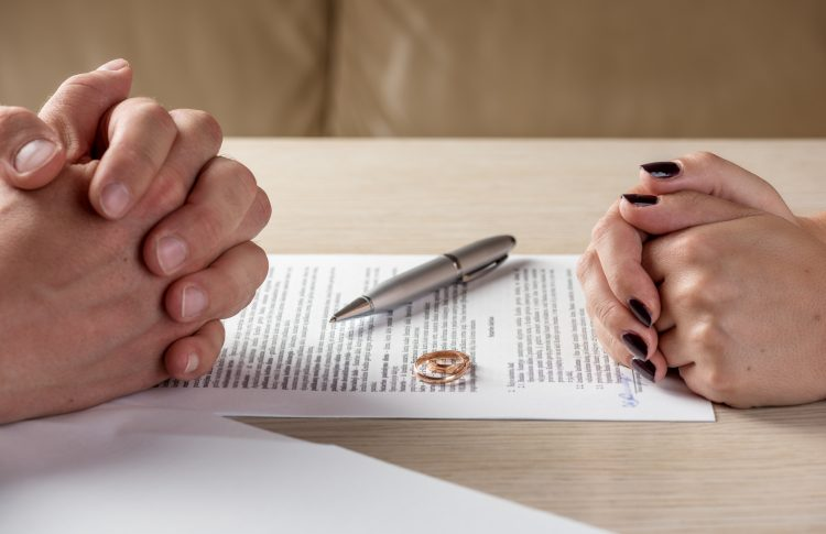 Hands of wife and husband signing divorce papers