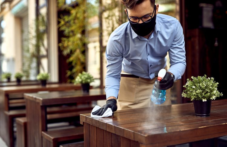 Waiter wearing protective face mask while disinfecting tables at outdoor